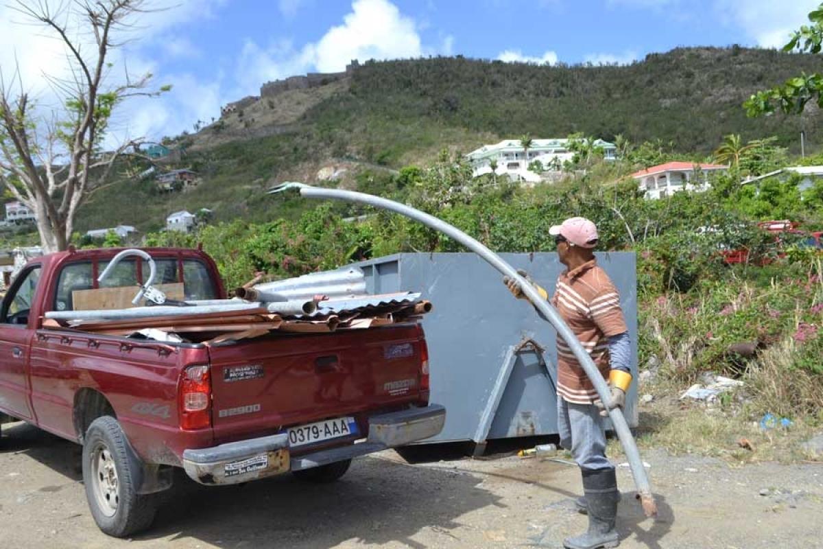 Anthony, de Colombier, remplit la benne avec ce qu'il a sorti de chez lui.